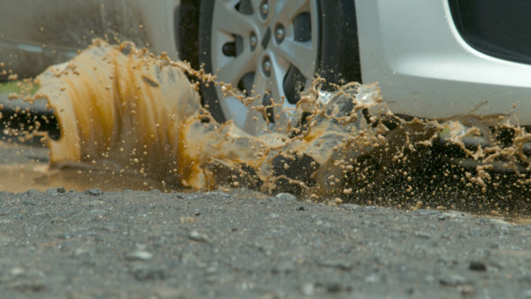 CLOSE UP: Silver vehicle drives into muddy puddle of water on black asphalt road